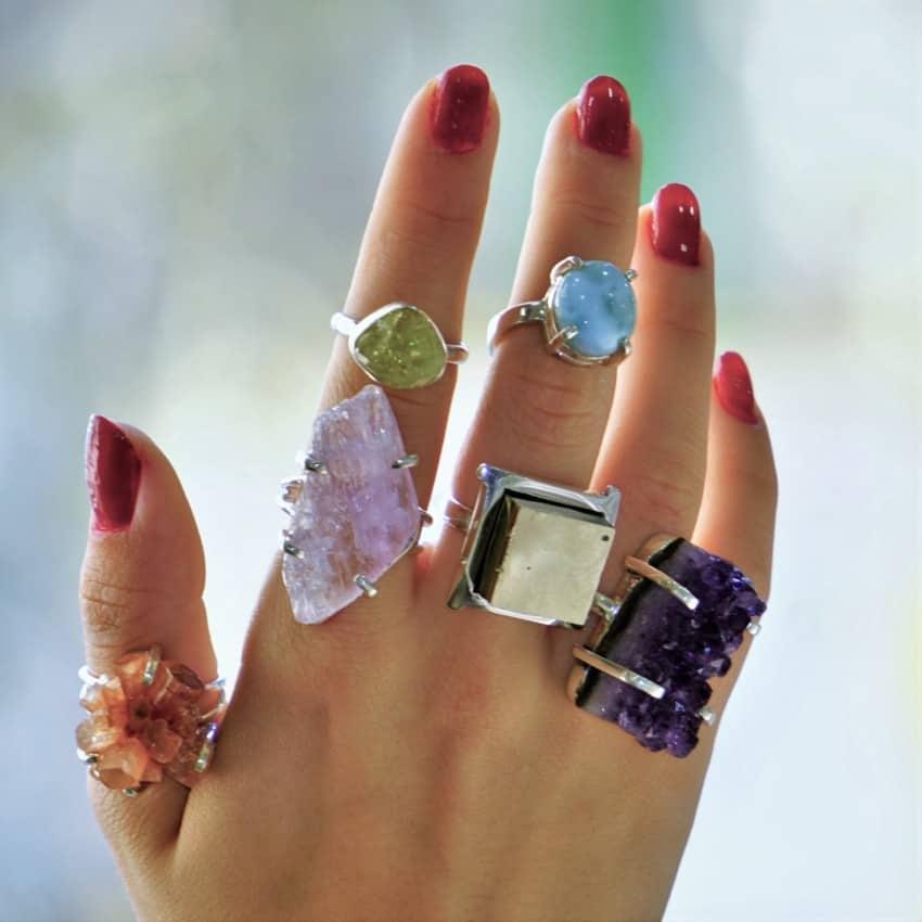 Mano femenina mostrando algunas de las últimas novedades en anillos de piedras naturales.
