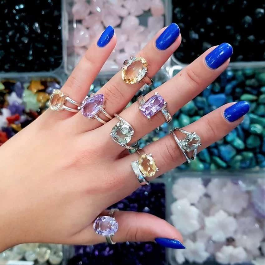 Selección de anillos de piedras de cuarzo amatista, citrino y prasio realizados en plata. Piedras talladas transparentes con multitud de diseños mostrados en los dedos de la mano.