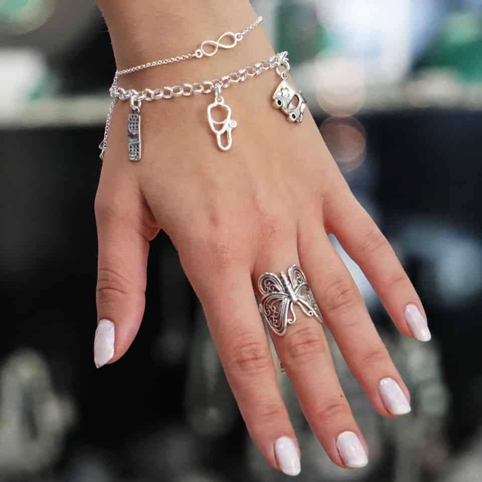 Pulsera infinito, pulsera de la enfermera y anillo de mariposa, todos mostrados en dedos y muñeca.