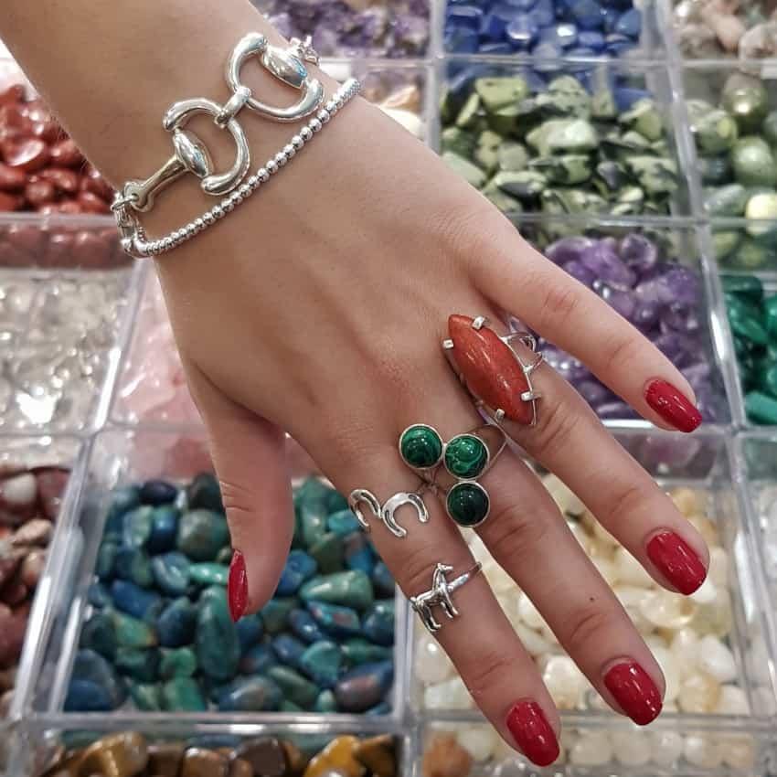 Multiples joyas en esta fotogracía, pulsera estribos, pulsera bolas 3 mm. anillo caballo, anillo herradura, anillo tres piedras de malaquita y anillo raíz de coral marquise.