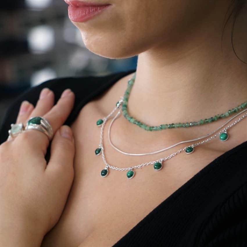 Joyas de color verde, gargantilla de chapas de malaquita, gargantilla esmeralda, anillo malaquita y anillo de fluorita mostrados en cuello y mano