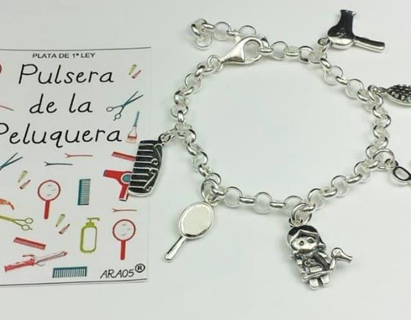 Preciosa pulsera fabricada en plata de ley 925 que lleva colgantes con motivos relacionado la peluquería: Un secador de pelo, peine, cepillo, alisador y tijeras.