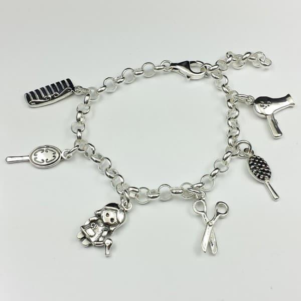 Preciosa pulsera fabricada en plata de ley 925 que lleva colgantes con motivos relacionado con la peluquería: peine, cepillo, peluquera, tijeras, alisador de pelo y secador de pelo.