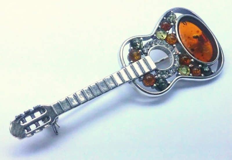Broche de Ámbar con forma de Guitarra fabricado en plata.