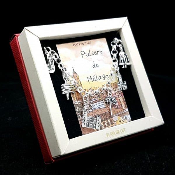 Pulsera fabricada en plata que lleva colgantes con motivos relacionado con la ciudad de Málaga: chancla playera, espetos, Catedral La Manquita, la flor de biznaga, el faro La Falora y el vendedor callejero Cenachero.