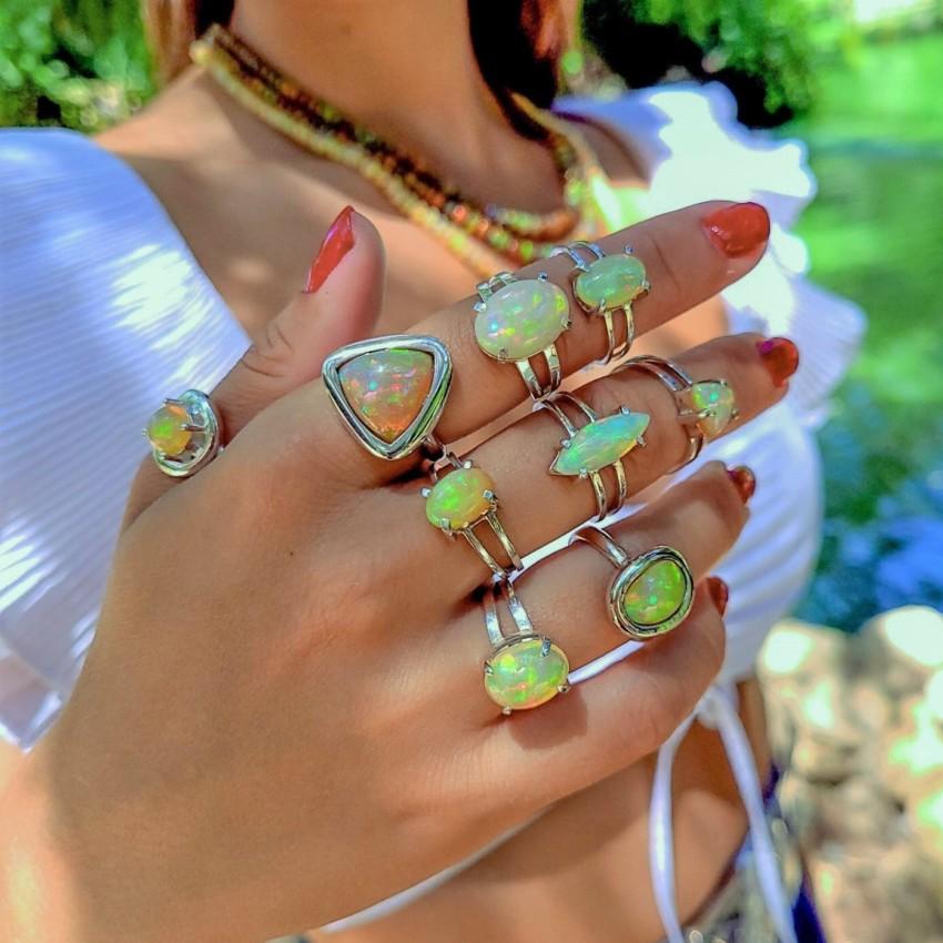 Mano mostrando nueve anillos de plata con ópalo