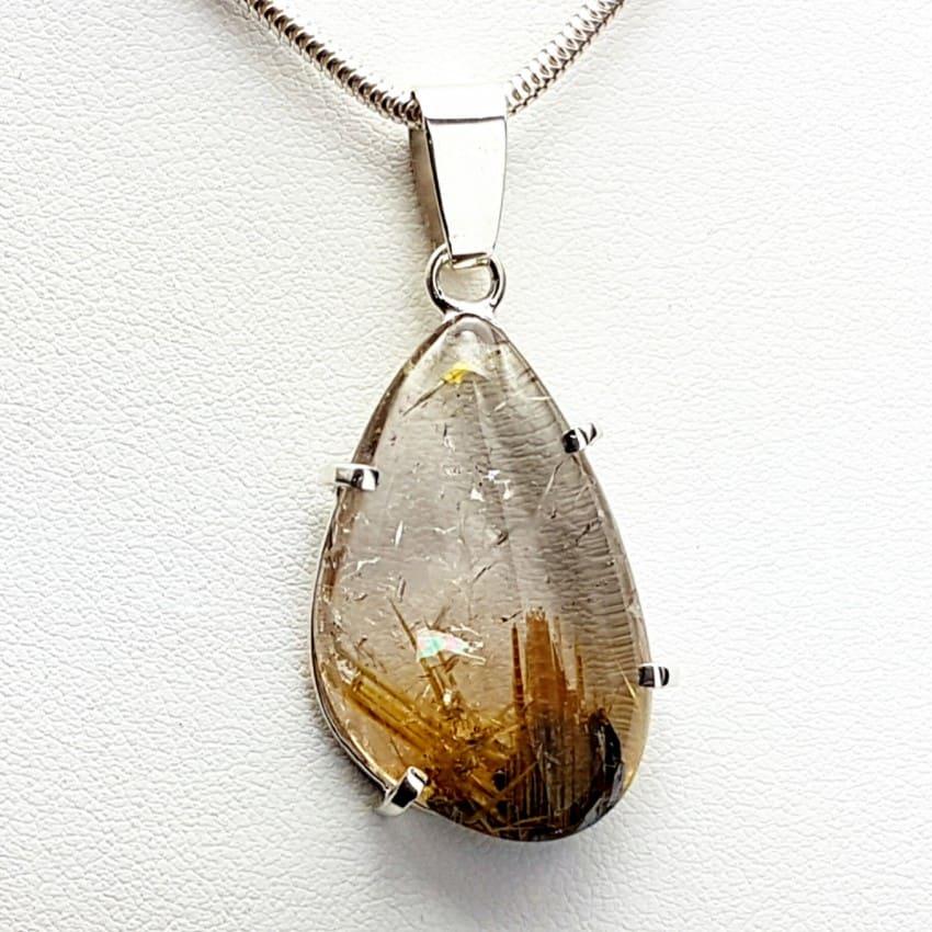 Colgante de Cuarzo rutilado con nacimiento en cristal de hematites fabricado en plata.