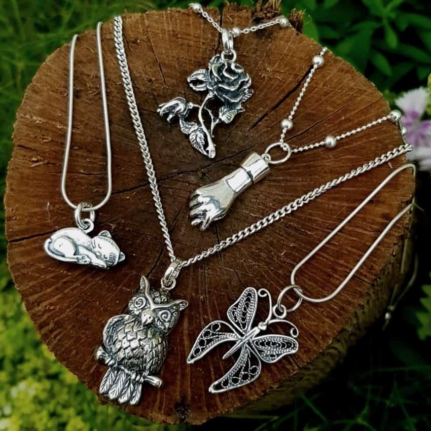 Selección de colgantes en plata. Flor, puño de la suerte, gato, buho y mariposa.