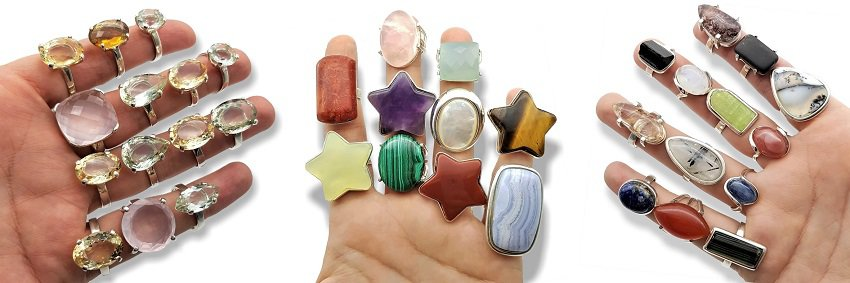 Manos llenas de anillos de piedras naturales en plata