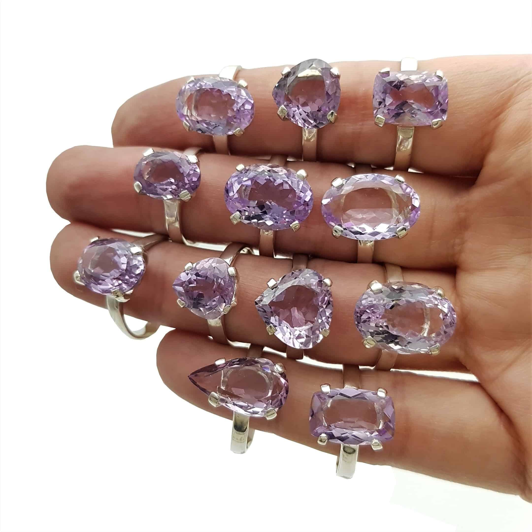 Dedos llenos de anillos de piedras semipreciosas de cuarzo amatista en plata