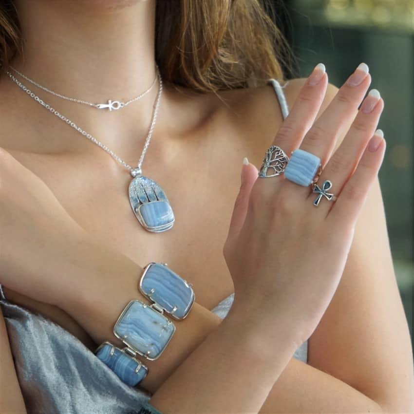 Look de pulsera, anillo y colgante de calcedonia azul combinadas con otras joyas, con la cruz y el árbol de la vida