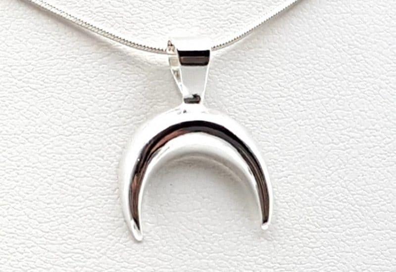 Colgante con forma de media luna fabricado en plata