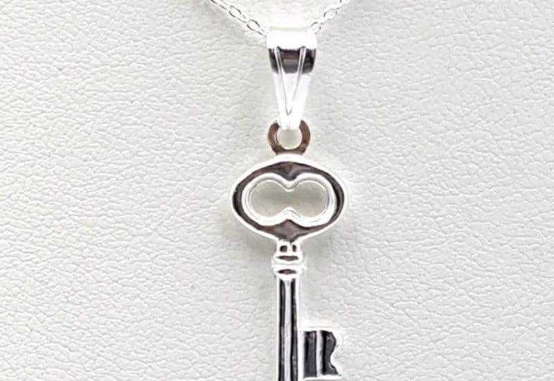 Colgante con forma de llave y gargantilla fabricados en plata de ley