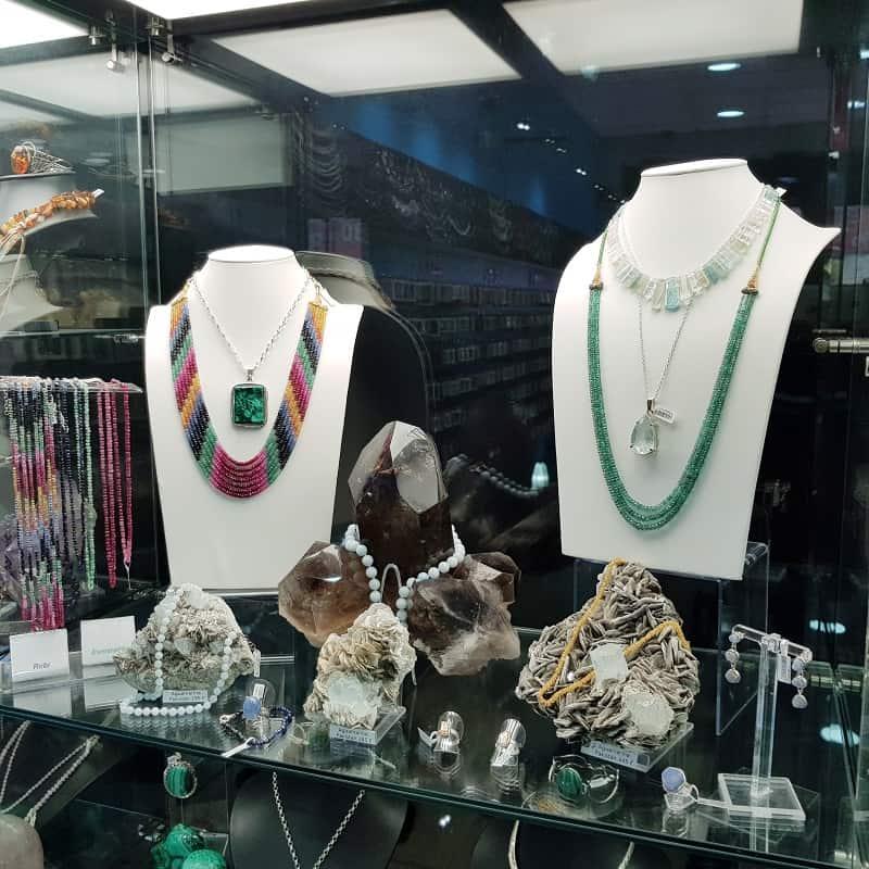 Detalles del interior de una de las vitrinas de laminadeplata.com compuesto por minerales de colección, collares y otros complementos de plata.