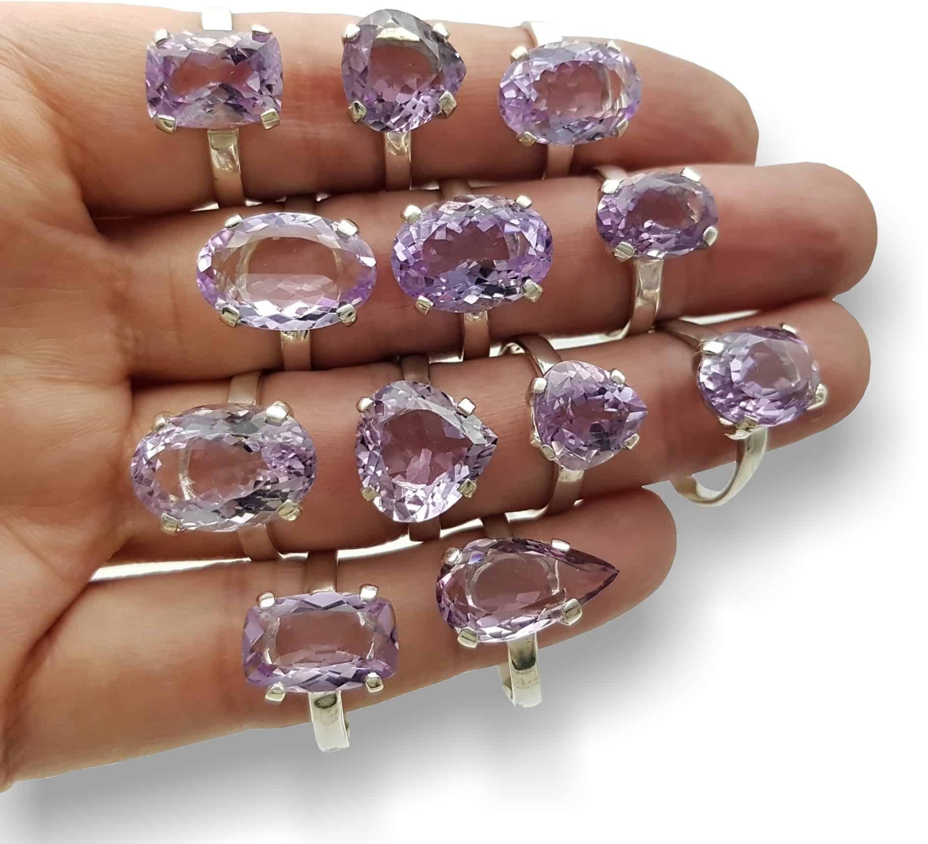 Foto de la mano izquierda mostrando 12 anillos de plata y cuarzo amatista facetada