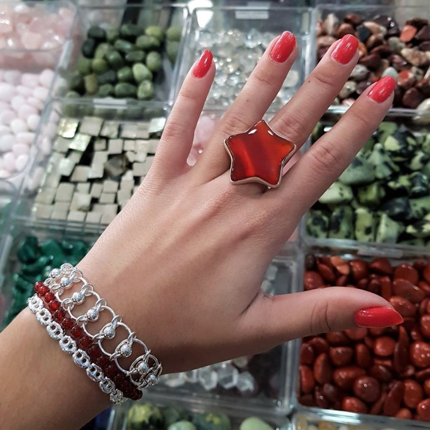 Fotografía que muestra una mano femenina con el anillo de cornalina con forma de estrella