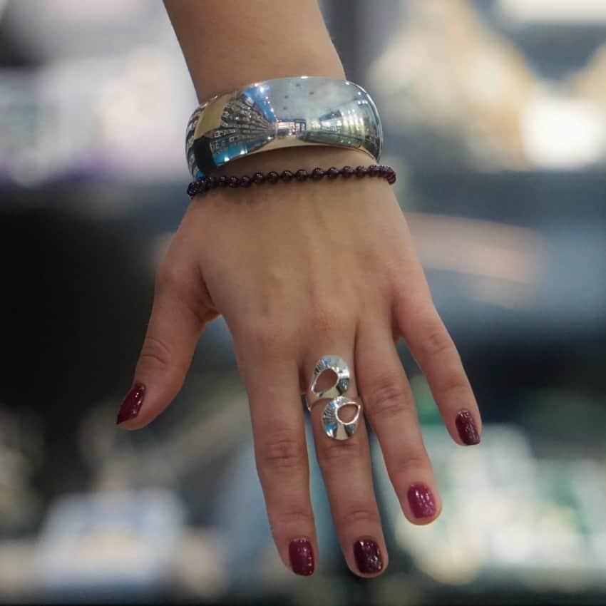 Fotografía que muestra como queda la pulsera de media caña, una anillo zigzag y la pulsera de granate en una mano