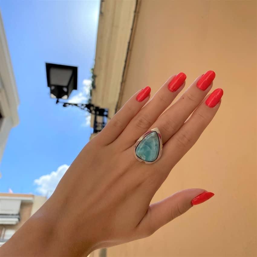 Anillo de larimar mostrado en la mano de una modelo justo al lado de nuestra tienda en Sevilla
