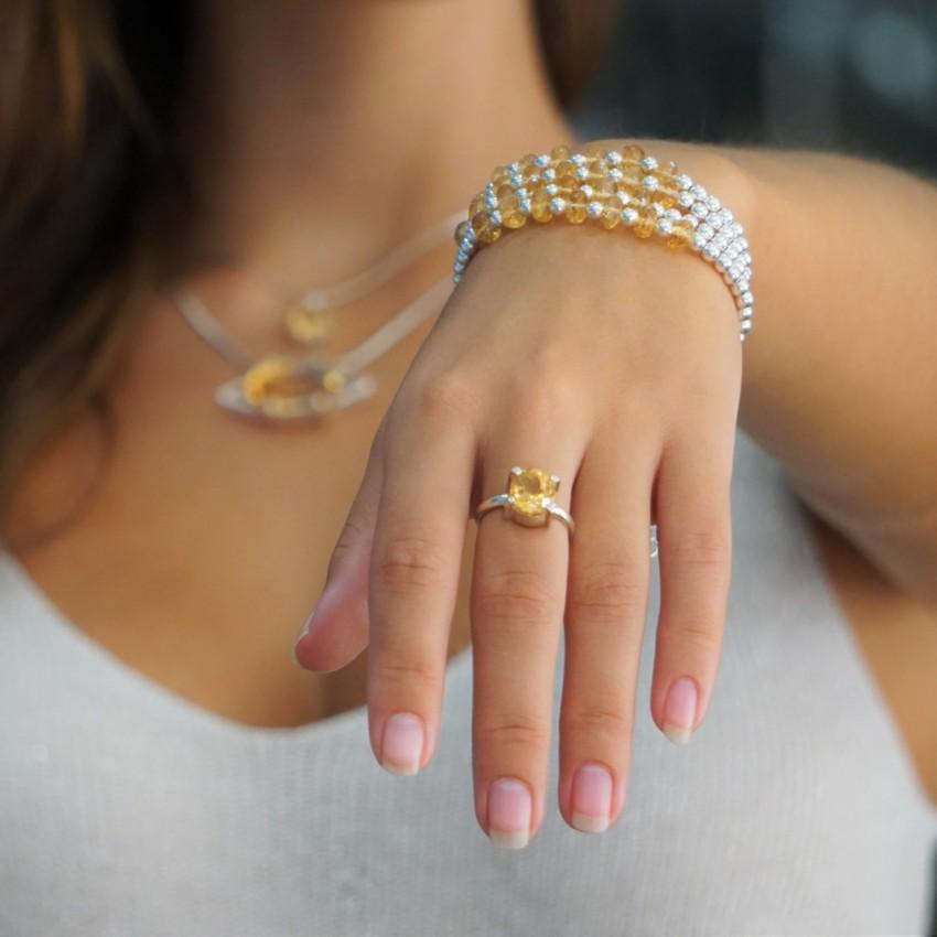 Luciendo joyas de cuarzo citrino en mano, muñeca y cuello