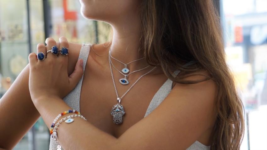 Joyas del Ojo Turco realizados en plata y mostrados puestos en cuello y muñeca.