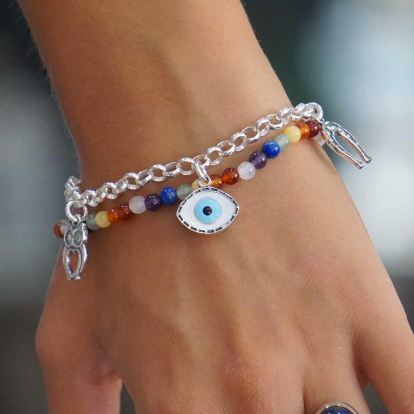 La pulsera de la buena suerte con su amuleto del ojo turco en primer plano junto a la pulsera de los chakras
