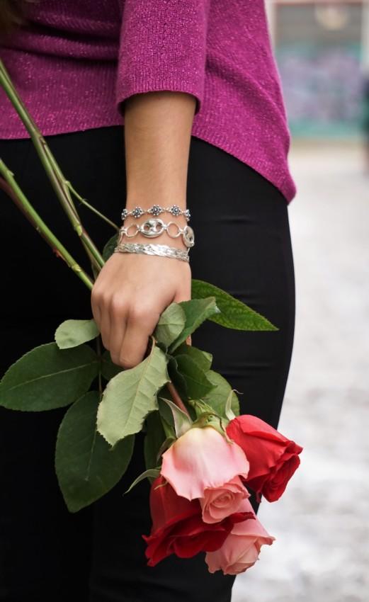 Luciendo pulseras de plata de LaMinadePlata.com llevando unas rosas por la calle.
