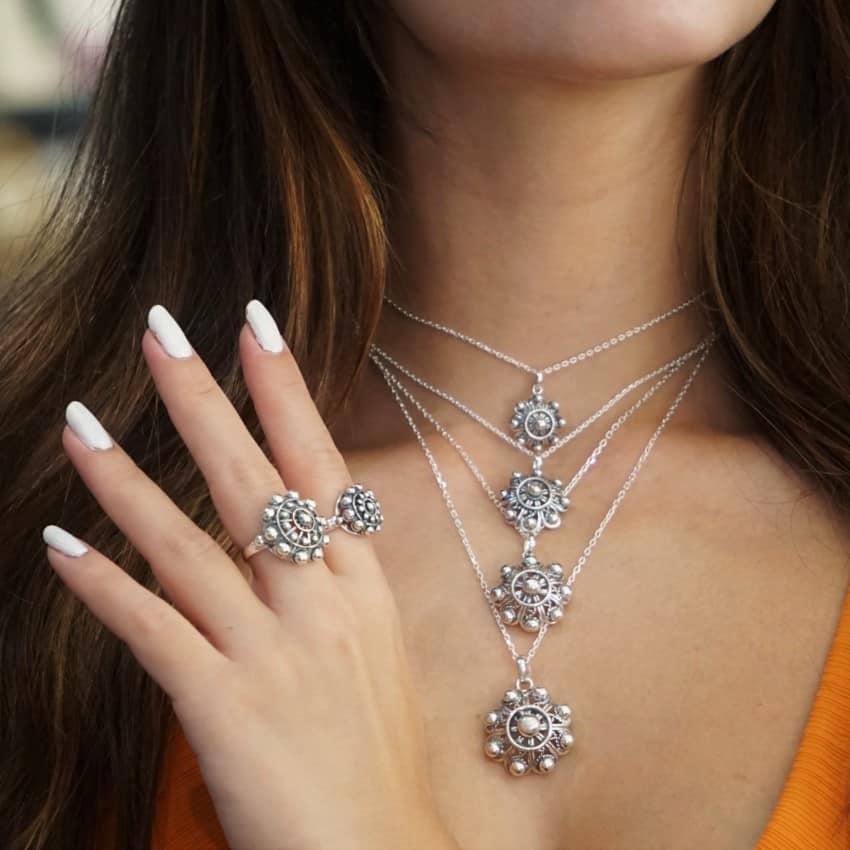 Foto demostración de como quedan los anillos y colgantes de charro en una modelo